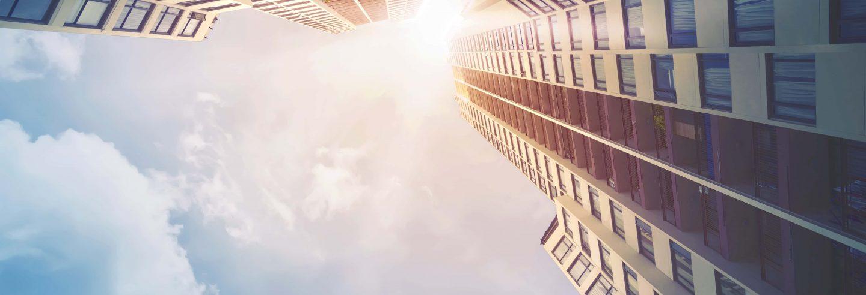 Blick nach oben in einen sonnigen Himmel entlang eines Mehrfamilienhauses